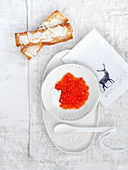 Salmon caviar on sour cream with butter crostini