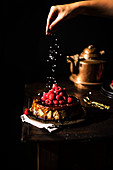 Vegan cheesecake with salted caramel sauce and raspberries