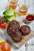Burger-Patties vom Angusrind auf Holzbrett