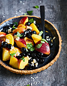 Steamed peach with blueberries and coconut flakes
