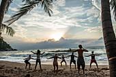 A yoga class on the beach on the island of Koh Phangan, Thailand