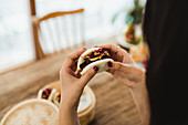 Hands of woman holding traditional Asian sandwich steamed bun with meat and vegetables