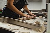 Bäcker rollt Teig für Fladenbrot aus