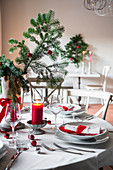 Christmas table setting with red and white decor and fir branches