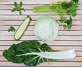 Grünes Gemüse und Kräuter auf Holzuntergrund