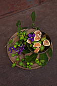 Fresh figs, fig twigs and clematis flowers on a wooden plate