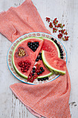 Watermelon slices with heart-shaped cut-outs filled with berries