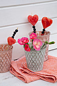 Fruit skewers with melon hearts and pink flowers in decorative glasses