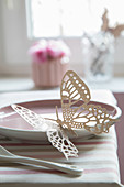 Delicate paper butterfly on plate decorating table
