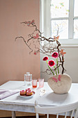 Branches decorated with butterflies and ranunculus on table