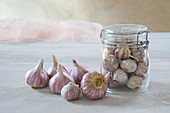 Fresh garlic bulbs in and next to swing-top jar