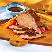 Roastbeef, teilweise in Scheiben geschnitten mit Sauce