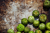Tomatillos on a rusty surface