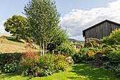 Ländlicher Garten mit Birke und Staudenbeet, Sitzgruppe im Schatten auf kleiner Terrasse