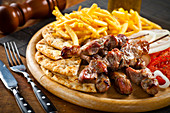 Greek pork souvlaki with fried potatoes and grilled bread