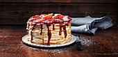 Pancake cake with jam, strawberries and icing sugar