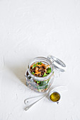 Broccoli salad with quinoa and chickpeas in a storage jar