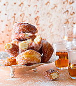 Sugared donuts served with glasses of tea