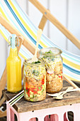 Glass noodle salad with vegetables and sprouts in glass jars for a picnic