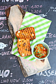 Tuna fish cake with tomato salsa on a specials board