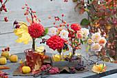 Floristische Dekoration mit Rosen, Dahlien, Zieräpfeln und Herbstlaub