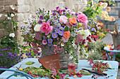 Herbststrauß aus Rosen, Astern, Fetthenne, Dahlie, Schneebeeren und Pfaffenhütchen