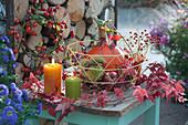 Herbstliche Dekoration mit Hokkaido-Kürbis, Äpfeln, Maronen und Hagebutten im Korb, Hagebutten-Kranz, Kerzen und Ranken vom Wilden Wein