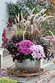 Silberner Kübel mit Chrysanthemen, Punktblume und rotem Federborstengras, Zweig mit Hagebutten und Clematisranke als Deko