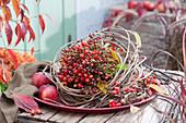 Strauß aus Hagebutten in Clematisranken auf Tablett, Äpfel und Zieräpfel als Deko