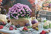 Tischdekoration mit Chrysantheme und Hornveilchen im Spankorb, Aubergine, Paprika, Blumenkohl, Marone, Chili und Mais