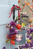 Kleiner Strauß aus Chrysantheme, Liebesperlenstrauch, Hagebutten und Lampions an Windlicht am Türgriff