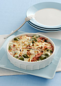 Spinach gnocchi gratin with ham and pine nuts