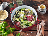 Pasta salad with salami, basil, olives, cucumber, onion, beansprouts, herbs and mustard