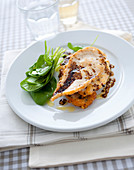 Chicken schnitzel in a parmesan coating with pepper sauce and spinach