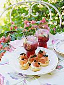 Canapes mit Räucherlachs und Kaviar, dazu Granatapfel-Caipiroska