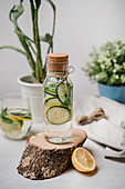 Small jar with cork filled with delicious lemonade with slices of fresh lemon and cucumber on wooden tray
