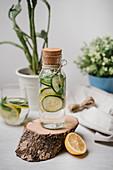 Flavoured Water mit Gurken- und Zitronenscheiben in Glasflasche