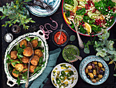 Mediterrean small dishes - Falafel, parsley, olives, salad with pearl couscous, olive, yoghurt sauce and pesto