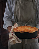 Man holding homebaked pie with crust