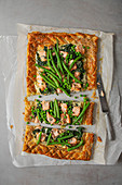 Puff pastry salmon tart with dill cream cheese, spinach, beans and peas