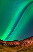 Aurora borealis over cliffs in Iceland