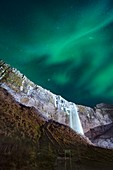 Aurora borealis over a waterfall in Iceland