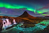 Aurora borealis over mountain and waterfall in Iceland