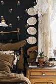 Baby-Fußabdrücke an schwarzer Blümchentapete über dem Bett