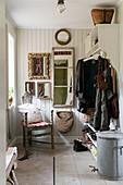 Dreibeiniger alter Stuhl im Eingangsbereich mit Garderobe