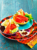 Slices of watermelon and bowl of chillies