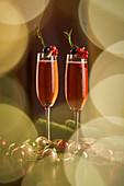 Zwei rote Cocktails mit Beeren und Rosmarin zu Weihnachten
