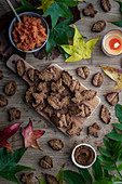 Tasty biscuits and autumn leaves placed on wooden table