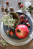 Autumnal table decoration of pomegranate, poppy seed heads and hydrangeas