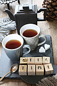 Holzwürfel mit der Aufschrift 'Teatime' auf Schieferplatte mit Teekanne und Teetassen